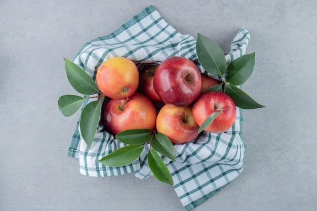 Appels opgestapeld in een mand bedekt met een handdoek op marmer