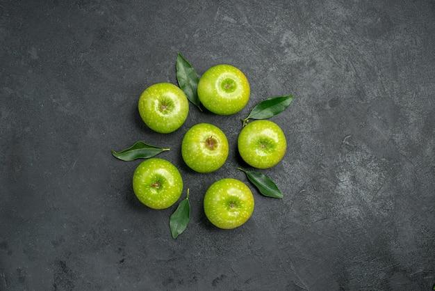 Appels zes smakelijke groene appels met bladeren op de donkere tafel
