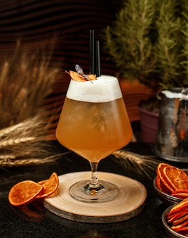 Appelsap in groot glas met ijs, zwart stro op een houten bord