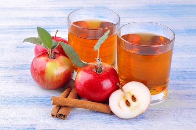 Appelsap met appels en kaneelstokjes op een houten achtergrond
