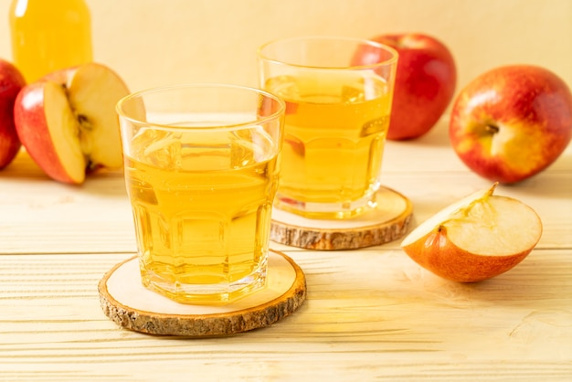 Appelsap met rood appelsfruit op houten lijst