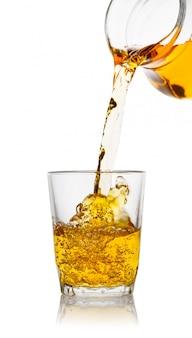 Appelsap stroomt uit de karaf in transparant glas