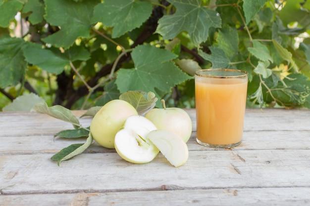 Appelschijfjes, appelsap en groene bladeren. zomerappeloogstconcept