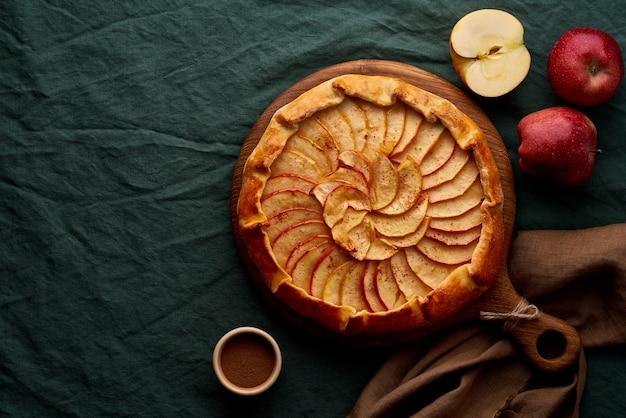 Appeltaart, galette met fruit, zoete gebakjes op donkergroen tafelkleed, kopie ruimte