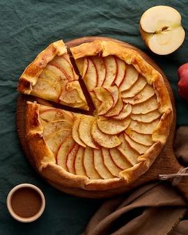 Appeltaart, galette met fruit, zoete gebakjes op donkergroen tafelkleed, verticaal, bovenaanzicht