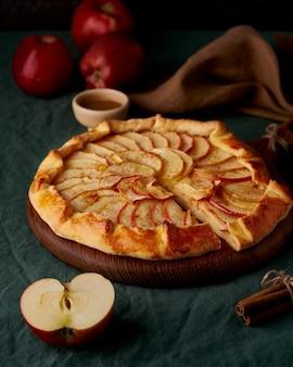 Appeltaart, galette met fruit, zoete gebakjes op donkergroen tafelkleed, verticaal
