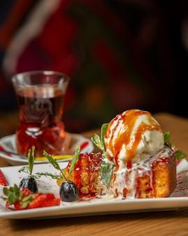 Appeltaart gegarneerd met ijsschep gegarneerd met druivenmost en aardbei