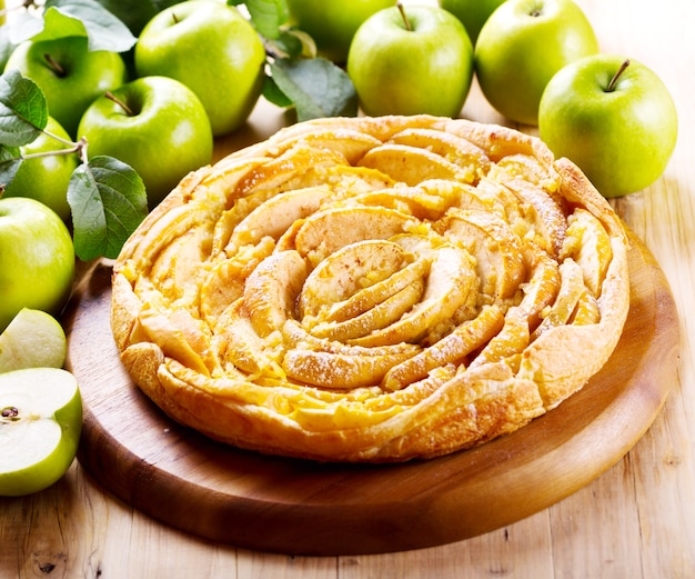 Appeltaart met vers fruit op houten tafel