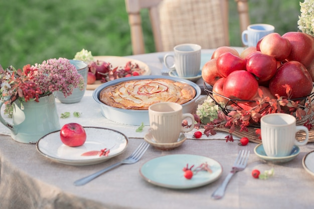 Appeltaart op gedekte tafel in de tuin op zonnige dag