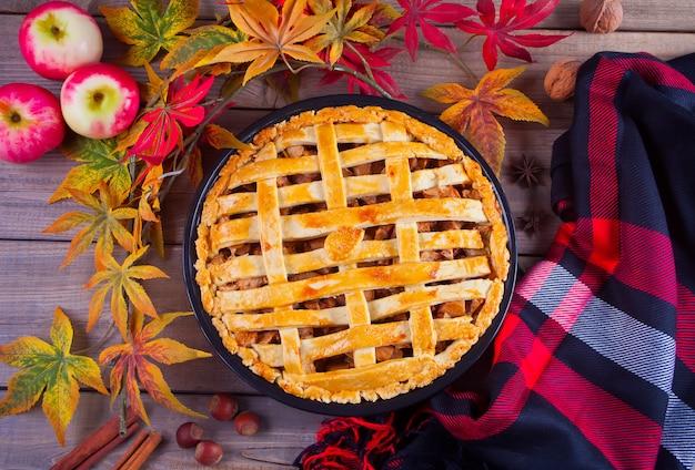 Appeltaarten op de houten tafel met herfstbladeren en plaid