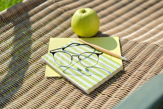 Apple boek potlood glazen notitieboekje op tuinstoel buiten. achtertuin studie.