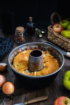 Apple bundt cake op donkere houten tafel, eieren, kaneel, vanille-extract
