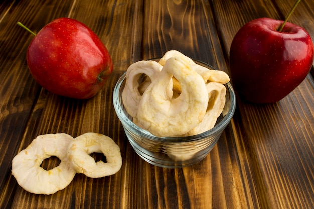 Apple-chips en rode appels op de houten tafel