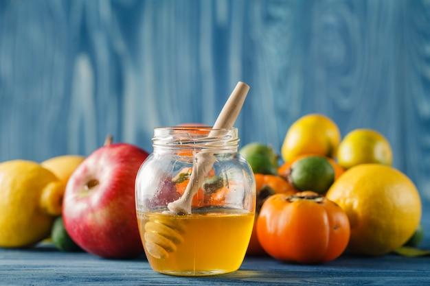 Apple en honing op houten tafel over blauwe achtergrond