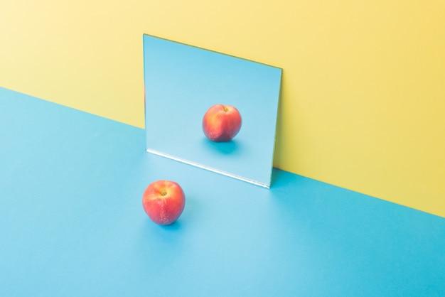 Apple op blauwe tafel geïsoleerd op geel in de buurt van spiegel