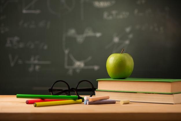 Apple op boek op leraarsbureau. terug naar schoolconcept