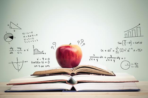 Apple op stapel open boeken met onderwijskrabbels en exemplaarruimte. onderwijs concept.