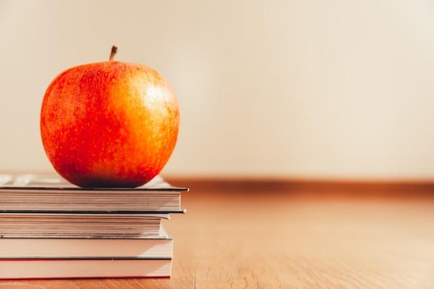 Apple over boeken op witte achtergrond en houten vloer, concept het gezonde leven worden geïsoleerd dat.
