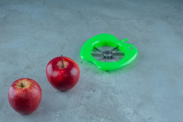 Apple-snijmachine en hele appels, op de marmeren achtergrond.