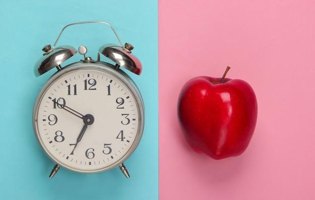 Apple, wekker op roze blauw. terug naar school. onderwijs concept