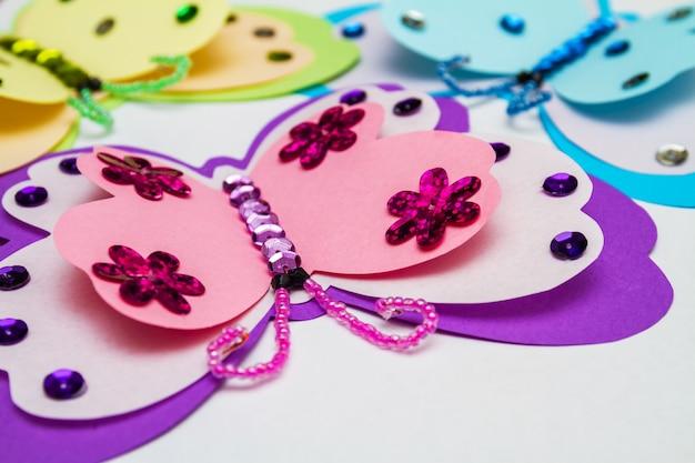 Applicatie gemaakt met hotmelt lijmpistool. drie vlinders van gekleurd papier, veelkleurige pailletten, pailletten en kralen.