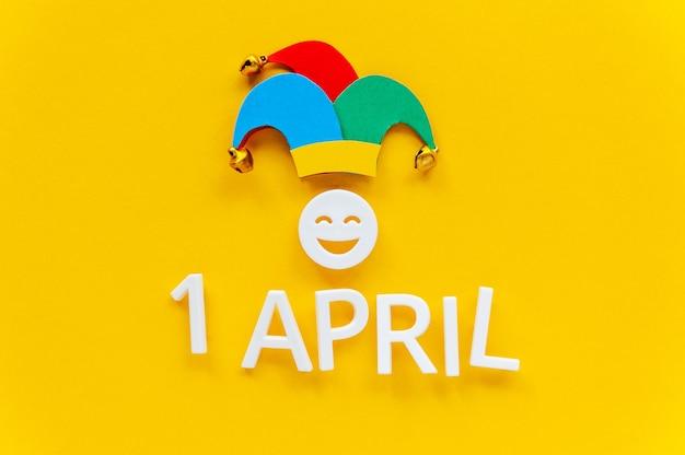 April dwazen dag over geel oppervlak met narrenhoed. eerste april kaart met lachend gezicht. kopieer ruimte, bovenaanzicht.