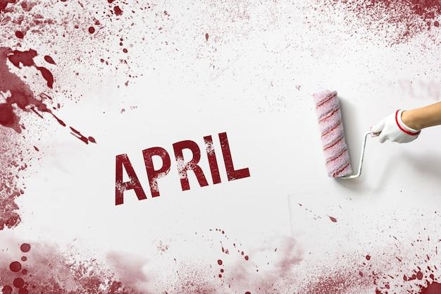 April. maand, kalendermaand. de hand houdt een roller met rode verf vast en schrijft een kalenderdatum op een witte achtergrond. lente, maand van het jaar concept.