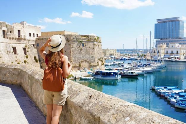 Apulië reist. achteraanzicht van jonge vrouwelijke backpacker in gallipoli, salento, italië.