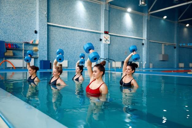 Aqua-aerobics, oefenen met halters in het zwembad
