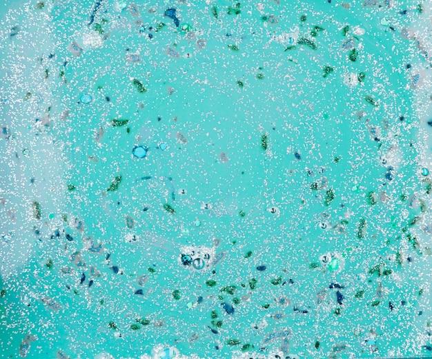 Aquamarijnvloeistof met kleurrijke stukjes
