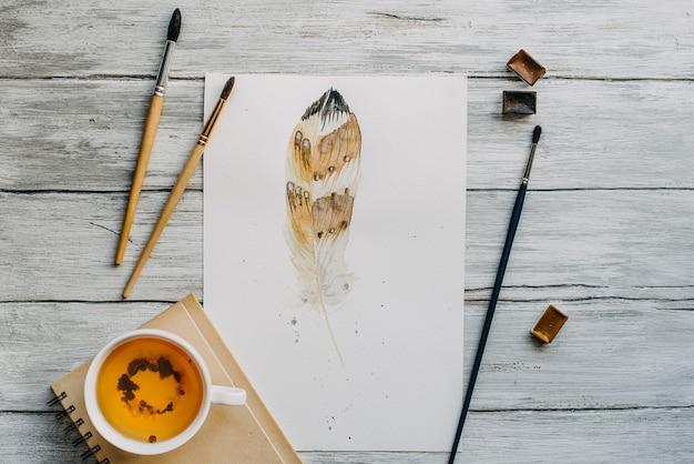 Aquarel met penseel en mok thee op houten textuur.