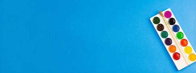 Aquarel schildert op een blauwe achtergrond.