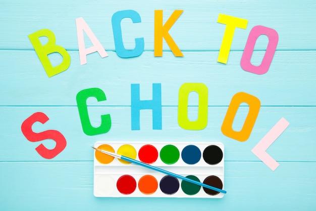 Aquarel verf set met inscriptie terug naar school op blauwe achtergrond