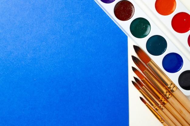 Aquarel verfdoos en set borstels op blauw en wit bovenaanzicht
