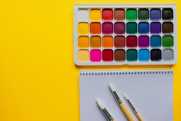 Aquarel verven en borstels op gele achtergrond, bovenaanzicht. creatieve artistieke mockup met copyspace. aquarelle schilderij