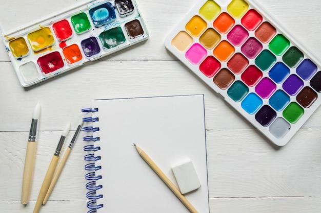 Aquarel verven, schetsboek en borstels, bovenaanzicht. creatieve artistieke mockup met copyspace. aquarelle schilderij