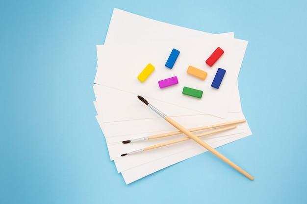Aquarelborstels van verschillende formaten liggen samen met aquarelpapier en verschillende kleuren op een blauwe achtergrond. lessen trekken. close-up, bovenaanzicht.