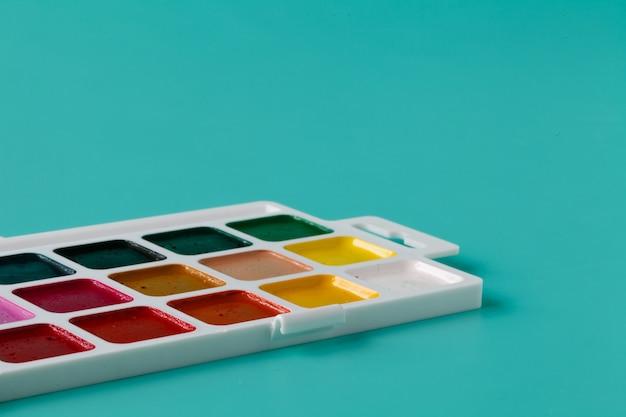Aquarelle kleuren in een plastic doos op een aquamarijn achtergrond