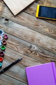 Aquarellen, kleurpotloden en schetsboek op houten tafel. platliggende foto met lege ruimte voor logo, tekst.