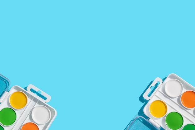 Aquarelverf in gele, oranje, groene en witte kleuren op een blauwe achtergrond. het concept van leren, school, creativiteit van kinderen, tekenen. bovenaanzicht, platliggend, minimalisme.