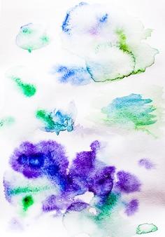 Aquarelvlekken en spatten van paars op het papier