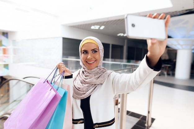Arabian neemt selfie in modern mall.