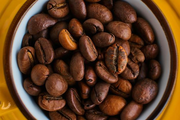 Arabica koffiebonen in heldere exotische gele kop op beige oppervlak met schaduwen van een palmboom Premium Foto