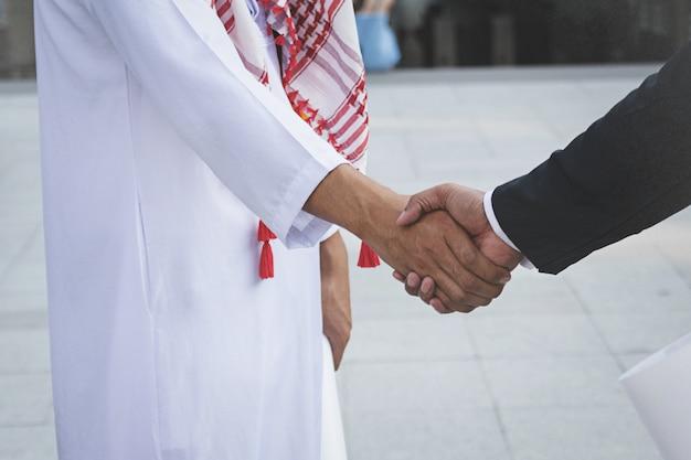 Arabisch zakenliedenarbeidershandenschudden op bouwwerf
