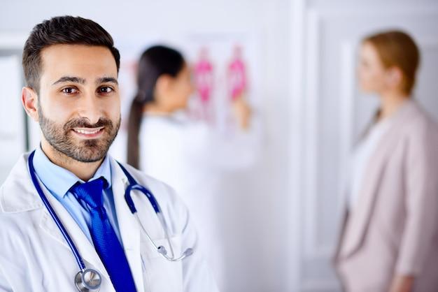 Arabische arts in het kantoor met tablet en stethoscoop, verpleegster die met patiënt aan de achtergrond werkt