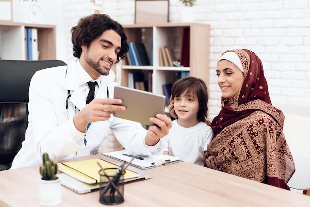 Arabische arts toont iets op de tablet.