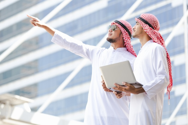 Arabische bedrijfsholdingslaptop die in stad werken