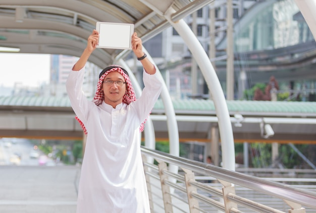 Arabische bedrijfsmens die tablet gebruiken en opheffen openlucht.
