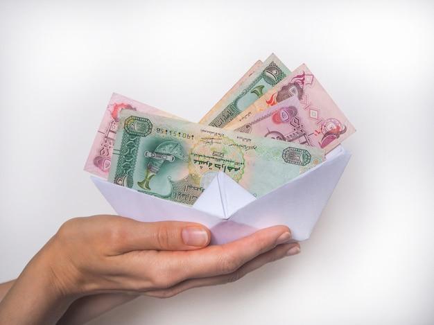 Arabische dirhams-munten worden vervoerd in een papieren boot. het concept van loopgraven en transfers.