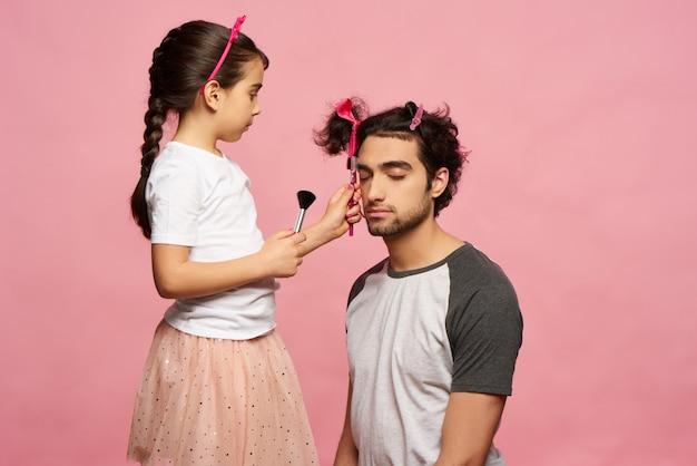 Arabische familie. het meisje doet make-up aan vader.